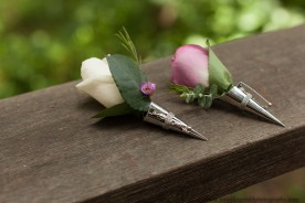 Wedding boutonnieres of pink and white roses in silver vase