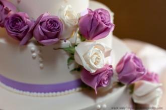 Purple and White roses on wedding cake