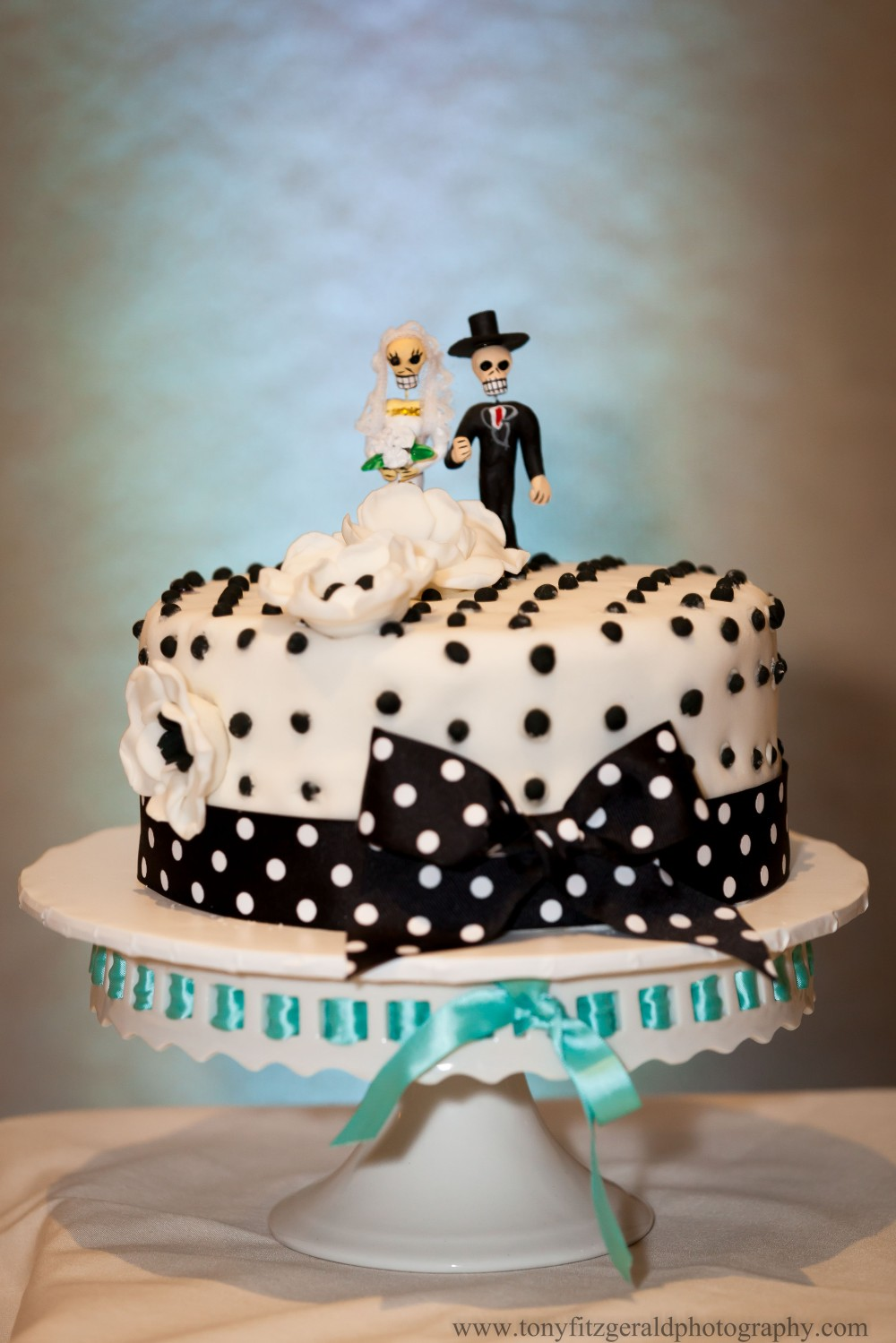 black and white polka dot wedding cake with day of the dead figurines as bride and groom