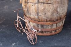 antique children's bike leaning against a wine barrel